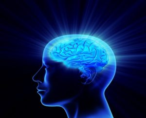 Blue side view of the human head with the brain glowing a lighter blue and light rays shooting off from the brain.